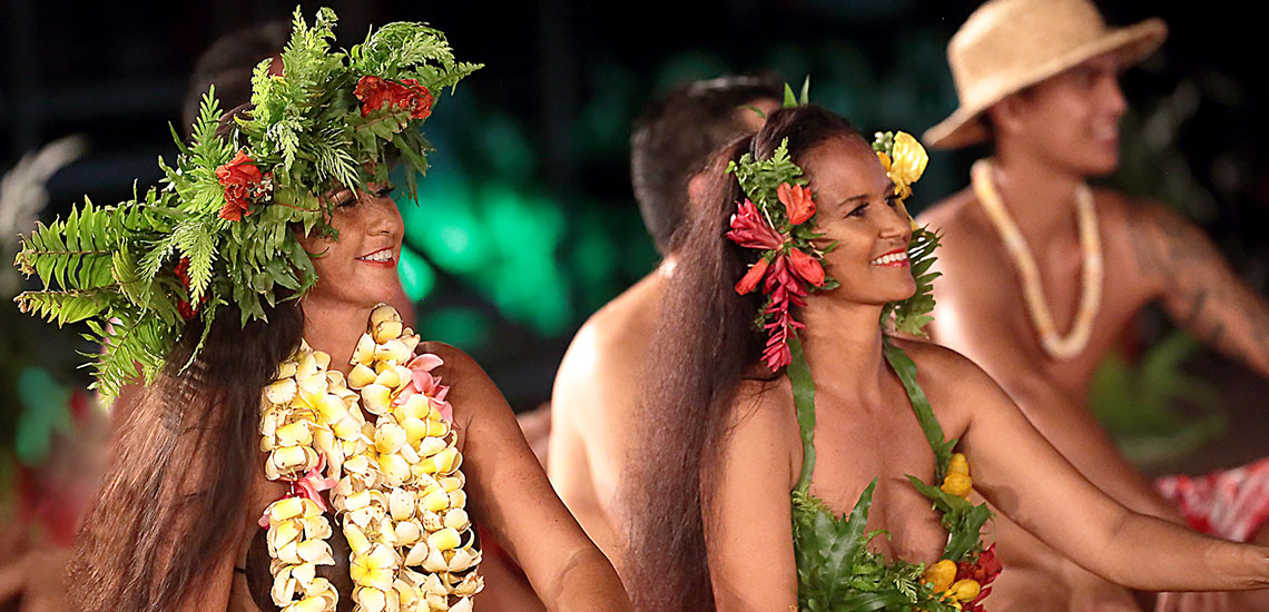 two women performing in tahitian dance costume