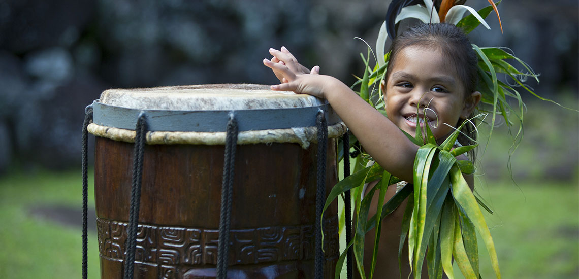 young tahitian boy playing large tahitian drum